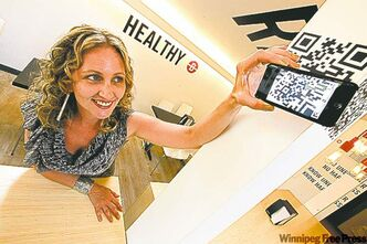 Erica Glasier, a Winnipeg marketer and blogger, scans a QR code at Unburger in Osborne Village. Glasier says the technology can be hit or miss and simple is better.