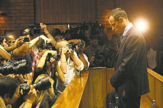 Photographers take photos of athlete Oscar Pistorius at his bail hearing Friday.