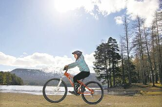 Cycling past Loch an Eilein at Rothiemurchus Estate in the Cairngorms National Park.