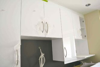 Kitchen cabinets are white thermofoil with soft-close hinges and stainless steel handles.