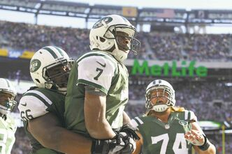 New York Jets quarterback Geno Smith (7) celebrates his touchdown run during the second half of their game against the New England Patriots at MetLife Stadium.