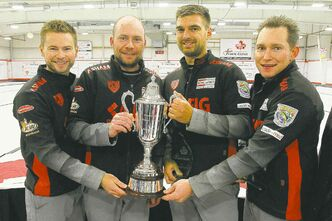 Mike McEwen (left) and his team of B.J. Neufeld, Matt Wozniak and Denni Neufeld hold the Dave Elias Memorial Trophy after winning the 2013 Canad Inns Prairie Classic.