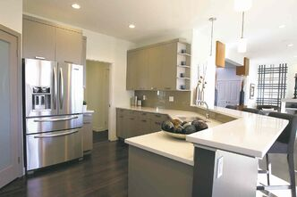The kitchen is outfitted with portobello maple cabinets, white quartz countertops and taupe glass tile backsplash.