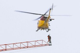 A search and rescue helicopter carries Adam Jastrzebski from a crane in Kingston, Ont., Tuesday.