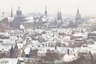 An aerial view of Amsterdam in winter. Here, centuries-old churches are converted into cultural centres and scenic canals weave their way past 17th-century, gabled buildings.