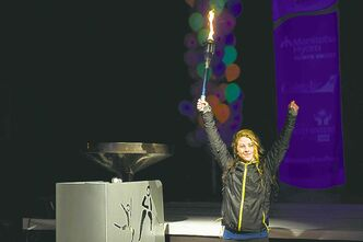 Torchbearer Amber Wiebe lights the cauldron during the opening ceremonies.