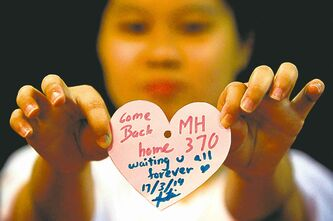 Lai Seng Sin / The Associated PressA woman holds a message for passengers aboard the missing jetliner on Monday.