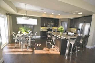 The kitchen includes a dinette area that is situated next to patio doors leading to a backyard deck.