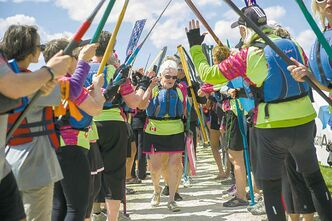 Jean Lyons is  given high fives by fellow dragon boaters after a flower ceremony at the 2014 River City Dragon Boat Festival