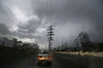 The view is distorted as the windshield of a car is covered in water as a driver makes his way through stormy weather after unusually heavy rainfall caused localized flooding in Sochi, Russia, Tuesday, Sept. 24, 2013. Many critics still complain about underdeveloped infrastructure in Sochi, where the Olympics will be held in February. (AP Photo/Sergei Grits)
