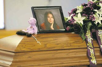 Purple flowers and a treasured teddy bear surround Tina Fontaine�s photograph on her casket. Purple was her favourite colour.