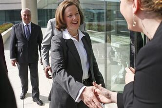 Alberta Premier Alison Redford greets an unidentified embassy official as she meets with Canada's Ambassador to the U.S. Gary Doer, obscured rear, along with Cal Dallas, Alberta Minister of International and Intergovernmental Relations, at the Canadian Embassy in Washington, Tuesday, April 9, 2013. (AP Photo/Charles Dharapak)