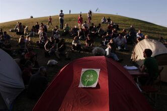 "A banner reading ""Yes we can"", is attached to a tent, as unemployed people and members of the unemployed assembly group camp in a park to protest against unemployment and precarious work in Madrid, Tuesday, June 11, 2013. (AP Photo/Andres Kudacki)"