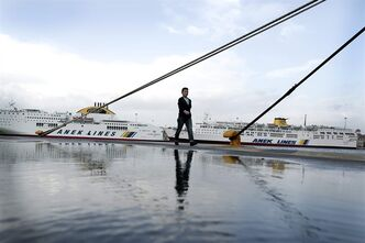 A woman walks in front of docked ships during a 24-hour general strike to proteset further austerity cuts, at the port of Piraeus, near Athens, on Wednesday, Nov. 6, 2013. The strike disrupted public transport across Greece, halted ferry and train services, shut down state-run schools and left state hospitals and the ambulance service functioning with emergency staff. (AP Photo/Petros Giannakouris)