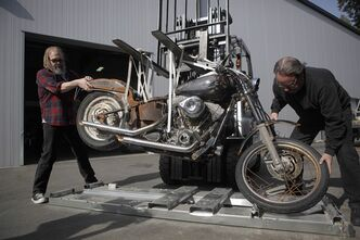 Ralph Tieleman (left) helps dealership owner Steve Drane, stabilize the 2004 Harley-Davidson Night Train that was swept to sea during the Japanese tsunami, in Langford, B.C. May 6, 2012. Ikuo Yokoyama's Harley is nearing the final stretch in its journey home. THE CANADIAN PRESS/Chad Hipolito