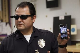 Los Angeles Police Sgt. Daniel Gomez demonstrates a video feed from his camera into his cellphone as on-body cameras are demonstrated for the media in Los Angeles Jan. 15, 2014. THE CANADIAN PRESS/AP -Damian Dovarganes