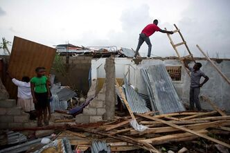 Residents repair their homes destroyed by Hurricane Matthew in Les Cayes, Haiti, Thursday, Oct. 6, 2016. Two days after the storm rampaged across the country