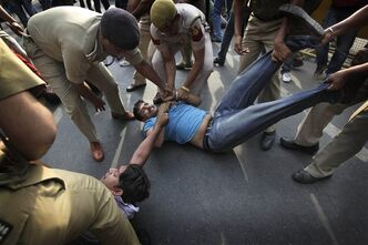 Indian policemen remove protestors shouting slogans outside th eprime minister's residence during a protest against the rape of a 5-year-old girl in New Delhi, India, Sunday, April 21, 2013. The girl was raped and tortured by a man who held her in a locked room in India's capital for more than two days. (AP Photo/Manish Swarup)