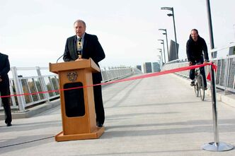 Local Government Minister Ron Lemieux speaks at the opening of the Disraeli Active Transportation Bridge on Oct. 3 as a cyclist rides along.