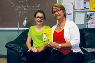 River East Transcona School DIvision educational assistant Shannon Schultz. who authored Faith has Freckles and Walter has Wheels. But did you know... is shown with Murdoch MacKay Collegiate student Abby Turczak, who does readings of the book for young students.