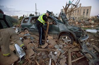 Police examine a crushed vehicule after a powerful storm ripped through Goderich, Ont. on Sunday, August 21, 2011. THE CANADIAN PRESS/ Geoff Robins