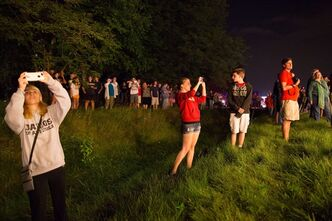 Onlookers watch and take photos as the electromagnet passes by on Butterfield Road in Glen Ellyn, Ill., Thursday, July 25, 2013 enroute to its new home outside Chicago on Friday. The electromagnet is 50 feet wide, weighs more than 15 tons and has taken a month to transport 3,200 miles from New York to Illinois. (AP Photo/Scott Eisen)