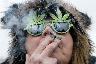 The Peace Tower is reflected in the sunglasses of a woman smoking a joint at the Fill the Hill marijuana rally on Parliament HIll in Ottawa on Saturday, April 20, 2013. THE CANADIAN PRESS/Justin Tang