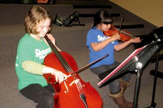 Kelsey Hall, 10, and Tyla Stagg, 9, run through Lean on Me in the music room at Elwick School. The pair are two of 100 Elwick and King Edward School students in the Winnipeg Symphony Orchestra's Sistema music program.