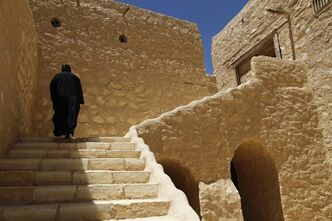 In this Tuesday, April 16, 2013 photo, a monk walks on the grounds of the ancient monastery of St. Anthony, southeast of Cairo, Egypt. In a cave high in the desert mountains of eastern Egypt, the man said to be the father of monasticism took refuge from the temptations of the world some 17 centuries ago. The monks at the St. Anthony's Monastery bearing his name continue the ascetic tradition. But even they are not untouched by the turbulent times facing Egypt's Christians, defiantly vowing their community's voice won't be silenced amid Islamists' rising power. (AP Photo/Manoocher Deghati)