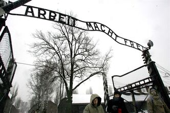 """FILE --In a Jan. 26, 2005 file photo, visitors walk under the notorious """"Arbeit Macht Frei"""" sign at the entrance gate of the Auschwitz Nazi concentration camp in Oswiecim, southern Poland. The special prosecutors' office that investigates Nazi war crimes said Tuesday Sept. 3, 2013 it is recommending charges against dozens of alleged former Auschwitz guards, opening the possibility of a new wave of trials almost 70 years after the end of World War II. Kurt Schrimm, the head of the Ludwigsburg federal prosecutors' office, said an investigation of about 50 alleged former guards turned up enough evidence to recommend that state prosecutors pursue charges of accessory to murder against 30 of them in Germany. (AP Photo/Herbert Knosowski/file)"""