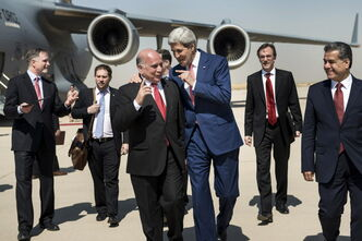 U.S. Secretary of State John Kerry, centre,  talks with Fuad Hussein, chief of staff for the Kurdish president, as they are accompanied by Kurdish foreign relations minister Falah Mustafa Bakir, right, and other officials at Irbil International Airport on Tuesday, June 24, 2014.