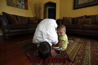 "Caleb Carter, 26, prays with his son Mahdi, 10 mo., at home in Dearborn, Mich., Tuesday, Sept. 6, 2011. For Carter, the road to becoming a Muslim took years, but Sept. 11, 2001 was a turning point _ specifically a high school teacher's hostile reaction that day to the terrorist attacks. ""I was a junior in high school at the time, taking a class called Nonwestern World Studies,"" said Carter, who then lived in Columbia, Mo., but now resides in the Detroit suburb of Dearborn, home to one of the nation's largest Muslim communities. ""For him, it was purely, 'This is what Islam teaches. We shouldn't be surprised.' He played the whole 'Islam equals terrorism card.'"" (AP Photo/Paul Sancya)"