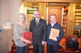 Betty Mayes and Bill Warren of Melita, with Gordon Goldsborough (centre) show the local history books they provided for digitization as part of the Manitobia project.