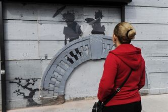 FILE - In this Oct. 19, 2013, file photo, a woman looks at work by British graffiti artist Banksy in New York's Brooklyn Borough. The secretive street artist ended his self-announced month-long residency in New York with a final piece of graffiti, a $615,000 painting donated to charity and a debate: Is he a jerk or a genius? (AP Photo/Alyssa Goodman, File)