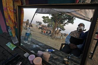 FILE - In this Friday, Nov. 23, 2012 file photo, an Indian man gets a shave during the annual cattle fair in Pushkar, Rajasthan, India. In October 2013, Procter & Gamble has introduced Gillette Guard, a low-cost razor designed for emerging markets like India. (AP Photo/Rajesh Kumar Singh)