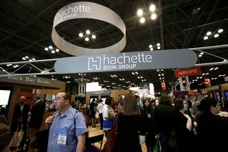 FILE - In this May 29, 2014 file photo, visitors walk through the Hachette Book Group's exhibition at BookExpo America, the annual industry convention in New York. Stephen King, Nora Roberts and Robert Caro are among the hundreds of authors who have added their names to an online letter criticizing Amazon.com for restricting access to works published by Hachette Book Group. (AP Photo/Mark Lennihan, File)