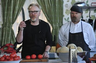 """In this undated image released by Discovery Channel, hosts Adam Savage, left, Jamie Hyneman appear in a mock kitchen to introduce teams on Discovery Channel's """"Unchained Reaction."""" for the episode's builds: Celebrating Tools! They show how a range of household tools can be used to great effect in the kitchen. In each episode, two five-person teams of engineers, designers and the like are given five days and a warehouse full of tools and materials to create a contraption based on a simple theme, such as """"light vs. heavy"""" or """"fire and ice."""" Then, Hyneman, Savage and a guest judge decide which one is the most inventive. The show premieres March 18, at 10 p.m. EST on Discovery. (AP Photo/Discovery Channel, Rahoul Ghose) (AP Photo/Discovery Channel)"""