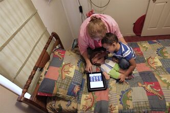 In this Friday, Oct. 21, 2011 photo, Denise Thevenot and her son Frankie Thevenot, 3, play with an iPad in his bedroom at their home in Metairie, La. About 40 percent of 2- to 4-year-olds (and 10 percent of kids younger than that) have used a smartphone, tablet or video iPod, according to a new study by the nonprofit group Common Sense Media. (AP Photo/Gerald Herbert)