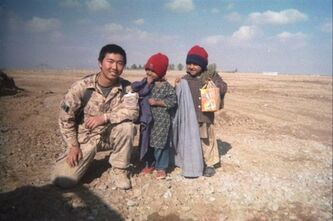 Canadian Cpl. David Hawkins poses with children in Afghanistan in a 2008 handout photo. Gravely injured troops who want to remain uniform are being booted from the military before they qualify for their pensions, despite assurances to the contrary from the Harper government. THE CANADIAN PRESS/HO-Cpl.David Hawkins