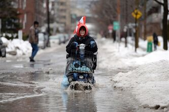 Jo-Anne D'Amour makes her way through a puddle following a storm in Ottawa on Monday, January 6, 2014. Temperatures are expected to drop 20 degrees by tonight. Freezing Rain, Winter Storm and Wind Chill warnings have been issued for the National Capital region. THE CANADIAN PRESS/Sean Kilpatrick