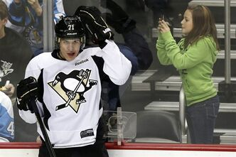 A young fan takes a picture of Pittsburgh Penguins' Evgeni Malkin (71), of Russia, during an NHL hockey practice at the Consol Energy Center in Pittsburgh, Monday, Jan. 14, 2013. (AP Photo/Gene J. Puskar)