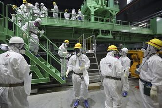FILE - In this Nov. 7, 2013 file photo, members of the media and Tokyo Electric Power Co. employees wearing protective suits and masks walk down the steps of a fuel handling machine after looking at the spent fuel pool inside the building housing the Unit 4 reactor at the Fukushima Dai-ichi nuclear power plant in Okuma, Fukushima Prefecture, Japan. Workers will begin removing radioactive fuel rods Monday from one of four reactors at the crippled Fukushima Dai-Ichi nuclear power plant, Tokyo Electric Power Co. said. The painstaking and risky task is a crucial first step toward a full cleanup of the earthquake and tsunami-damaged plant in northeastern Japan. (AP Photo/Tomohiro Ohsumi, File)