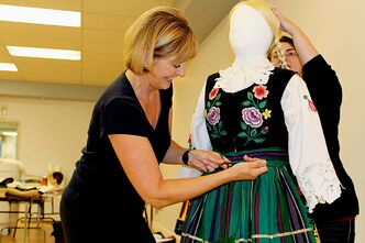 Christine Tabbernor, president of the Ogniwo Polish Museum Society board (left), and Alycia Walichnowski, collections manager at the museum, adjust the costume on a mannequin in preparation for the museum's upcoming exhibit, Dance Through Time: A Reflection of Polish Folk Culture.