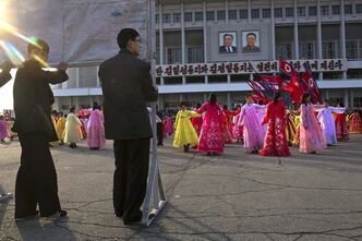 North Korean men hold a propaganda billboard as they watch mass folk dancing in front of Pyongyang Indoor Stadium in Pyongyang, North Korea, on Monday, April 15, 2013. Oblivious to international tensions over a possible North Korean missile launch, Pyongyang residents spilled into the streets Monday to celebrate a major national holiday, the birthday of their first leader, Kim Il Sung. (AP Photo/David Guttenfelder)