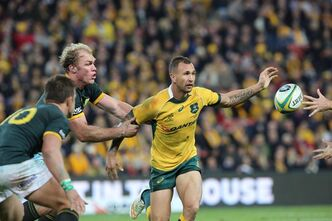 Australia's Quade Cooper, center, is held by South Africa's Schalk Burger, left, as he passes the ball during their Rugby Championship match in Brisbane, Australia, Saturday, July 18, 2015. (AP Photo/David Kapernick)