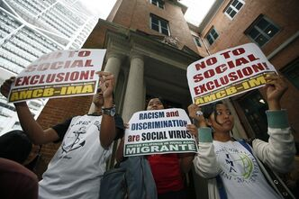 Supporters of Filipino migrant organizations hold placards outside the Court of Final Appeal in Hong Kong Monday, March 25, 2013. Hong Kong's top court ruled against two Filipino domestic helpers seeking permanent residency Monday, the final decision in a case that affects tens of thousands of other foreign maids in the southern Chinese financial hub. (AP Photo/Kin Cheung)