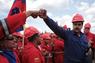 In this March 21, 2013 photo, released by Miraflores Presidential Press Office, Venezuela's acting President Nicolas Maduro fist bumps a worker of the state-run oil company PDVSA during a visit to the Orinoco oil belt in Venezuela. Maduro gathered hundreds of civil servants at the facility owned by PDVSA to ask support for his candidacy in the upcoming presidential elections to replace the late Hugo Chavez. The late leader transformed this country's enormous federal bureaucracy into nothing less than a political arm of the government, say former government workers and experts, with partisan loyalties trumping technical competence in hiring and ministries turning out thousands of civil servants for election year rallies. (AP Photo/Miraflores Presidential Office)
