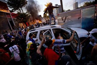 FILE - In this June 26, 2013 file photo, protesters destroy a car from a car dealership during a demonstration in Belo Horizonte, Brazil. Public approval of Brazilian President Dilma Rousseff's government has suffered a steep drop since protesters calling for a wide-range of reforms took to the streets all over Brazil in the past two weeks, according to Brazil's first nationwide poll released since the unrest began. (AP Photo/Victor R. Caivano, File)