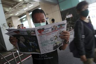 A Taiwanese man wearing a mask reads newspaper titled