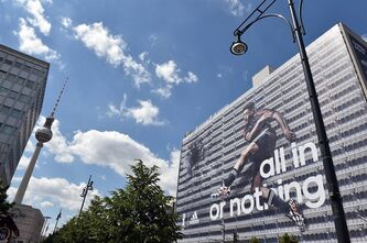 German national soccer player Mesut Ozil is visible on the facade of a publisher's building at Alexanderplatz square in�Berlin, Germany, Friday June 6, e 2014. Sportswear manufacturer Adidas has put up the advertisement on the entire facade of the building prior to the soccer World Cup tournament in Brazil. (AP Photo/dpa,Jens Kalaene)